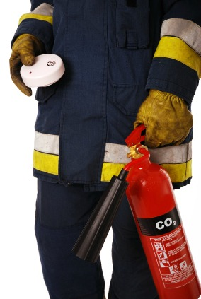firefighter holding extinguisher and smoke alarm