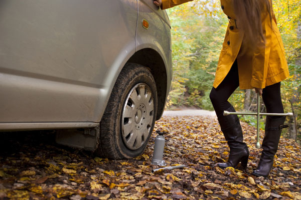 Woman changing her flat tire