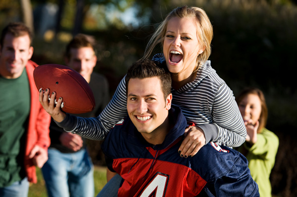Couple playing football with friends