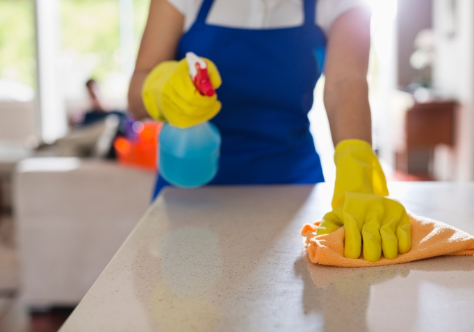 Woman cleaning countertop with yellow gloves on