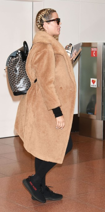 Khloé Kardashian spotted the Haneda airport in a camel colored fur coat and french braids