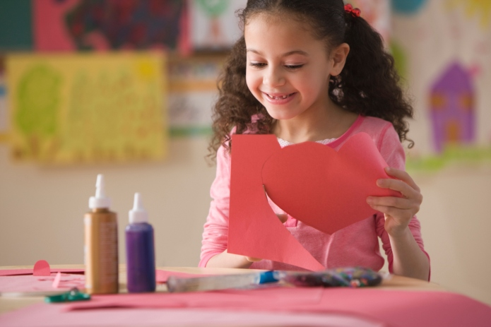 Hispanic girl cutting out Valentine's heart