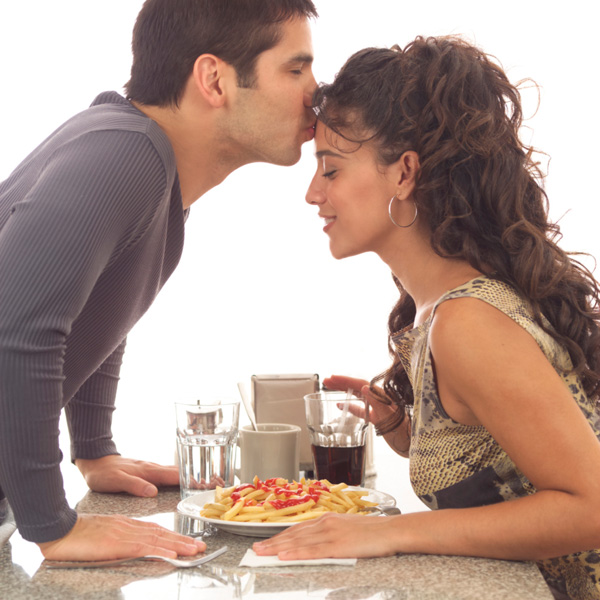 Woman getting kissed on forehead durning dinner