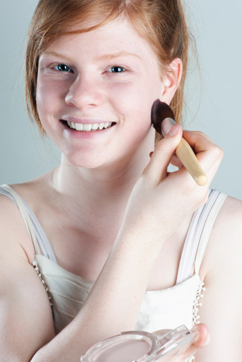 Girl applying powder foundation