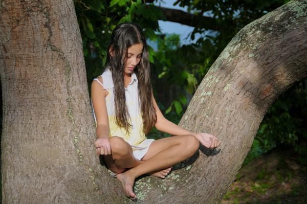 Child mditating in tree