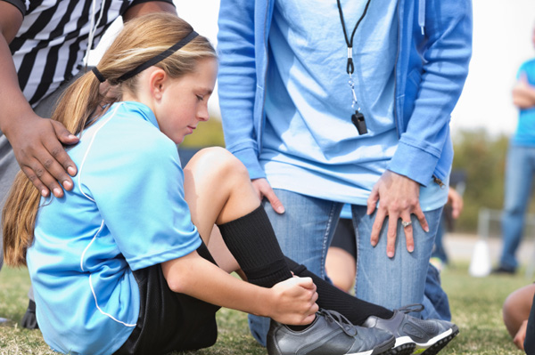 Girl soccer player with ankle injury