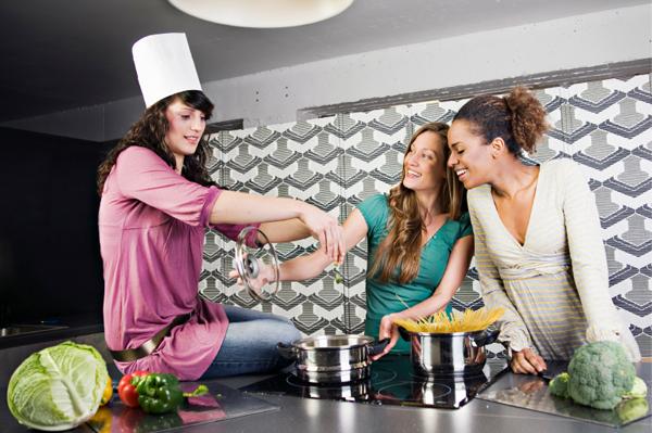 Girlfriends cooking in kitchen
