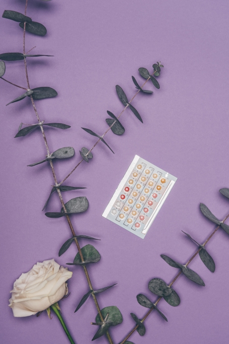 Birth control pill pack, rose and eucalyptus on purple background