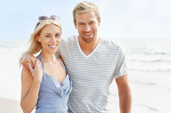 Happy couple on beach smiling