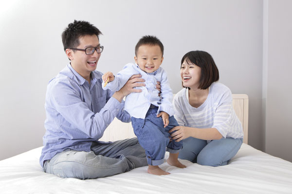 Happy family on bed together laughing