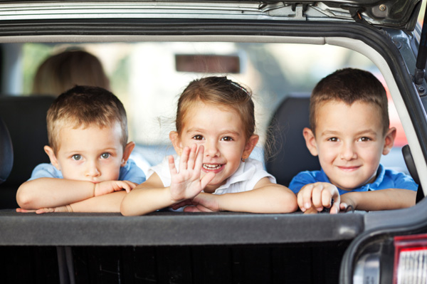 Happy kids in the back of a car