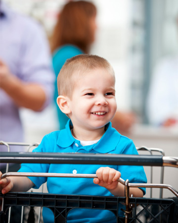 Happy toddler in shopping cart