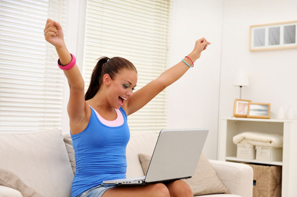 Woman cheering at computer