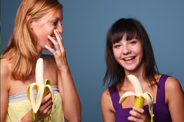 Happy woman eating bananas