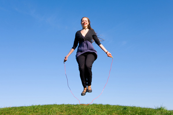 Happy woman jumping rope