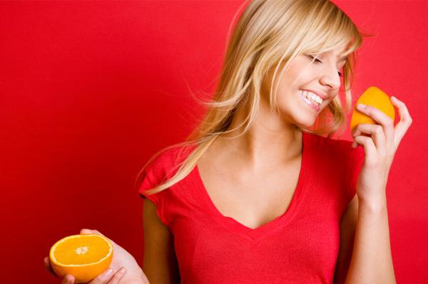 Happy woman eating oranges