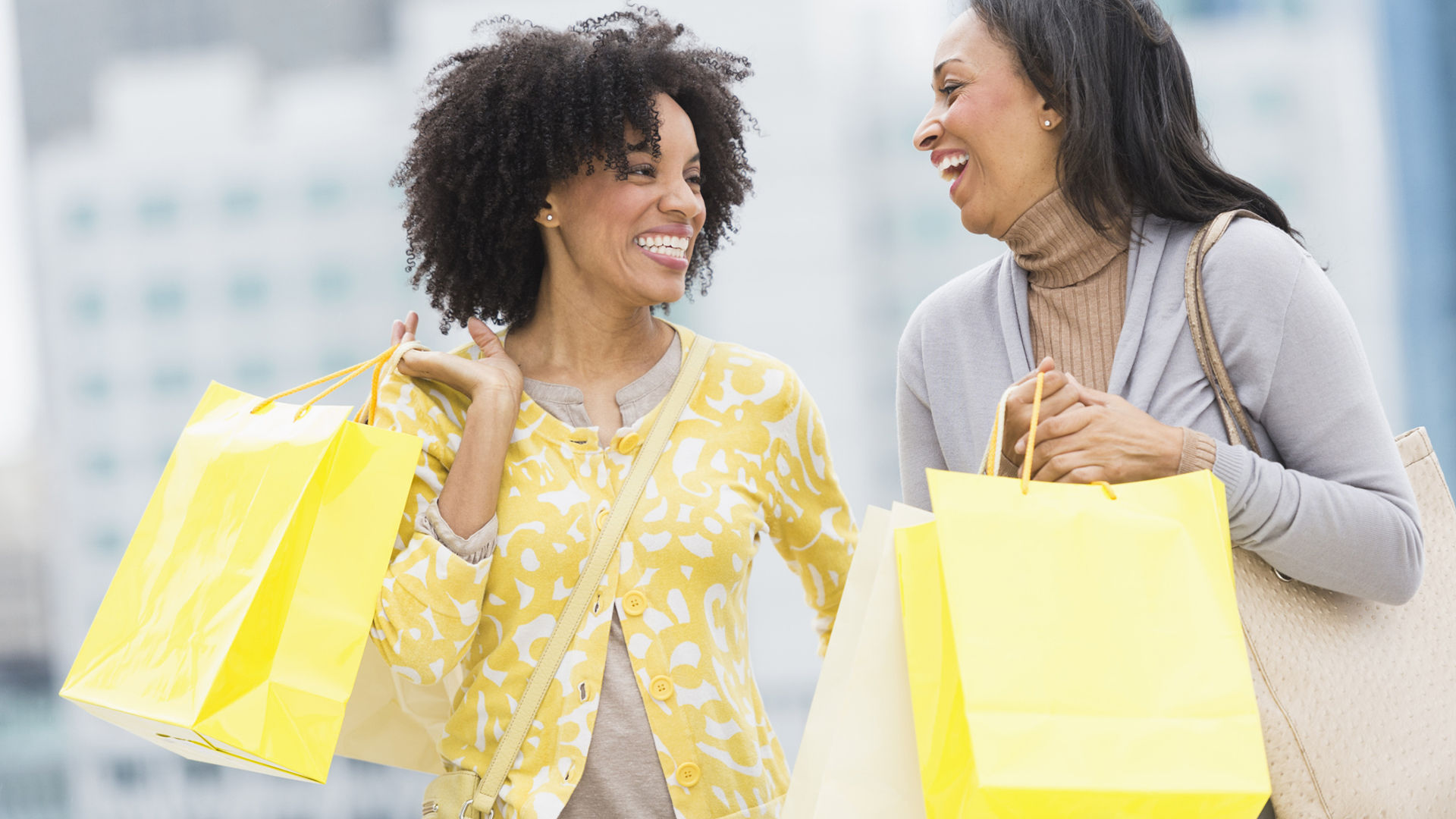 Happy women with yellow shopping bags | Sheknows.com