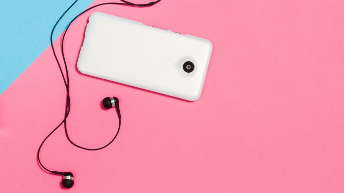headphones and cell phone pink background