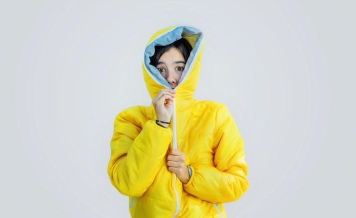 Girl closing zipper of wooden jacket