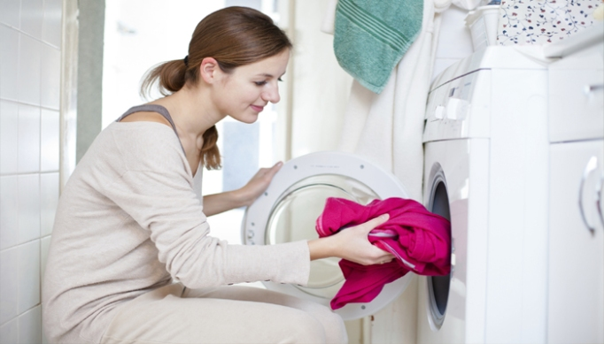 Woman putting clothes in dryer