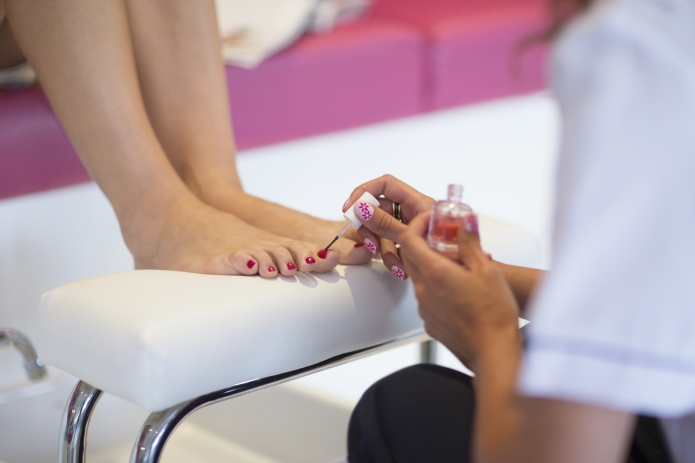 Nail technician applying fingernail polish to