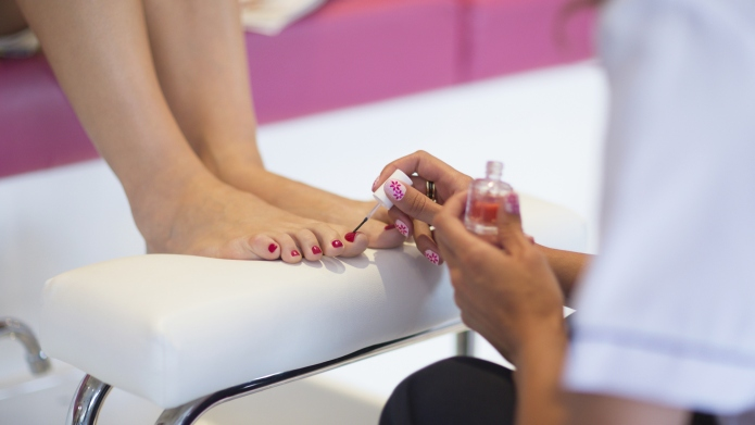 Nail technician applying fingernail polish to