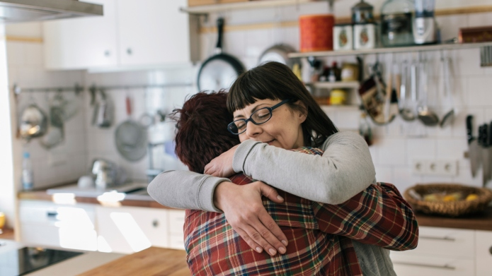 Lesbian Couple hugging in kitchen