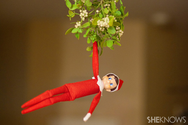 Elf on the Shelf idea 22: Elfie Rojo hanging under the mistletoe