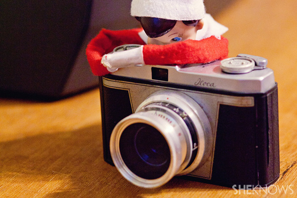 Elf on the Shelf idea 23: Elfie Rojo taking photographs