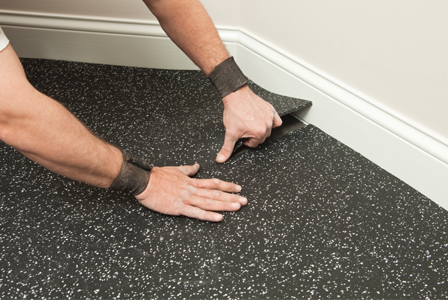 Man installing rubber flooring in garage