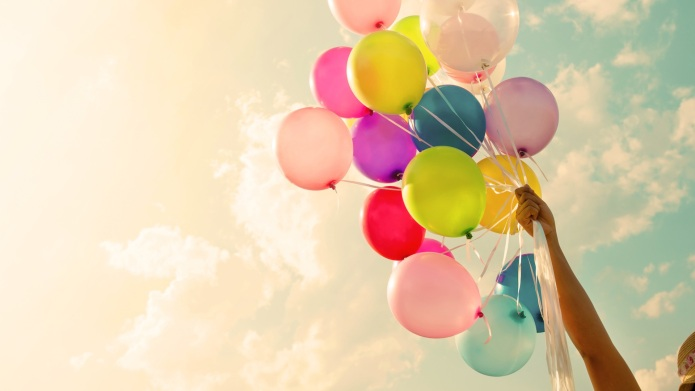Girl hand holding colorful balloons. happy