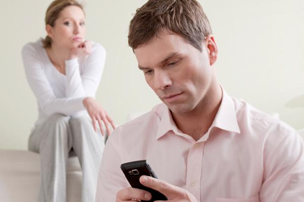 Woman watching husband on phone