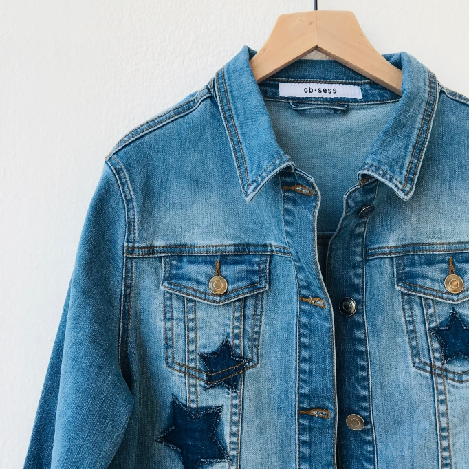 Denim jacket with blue stars hanging on white background
