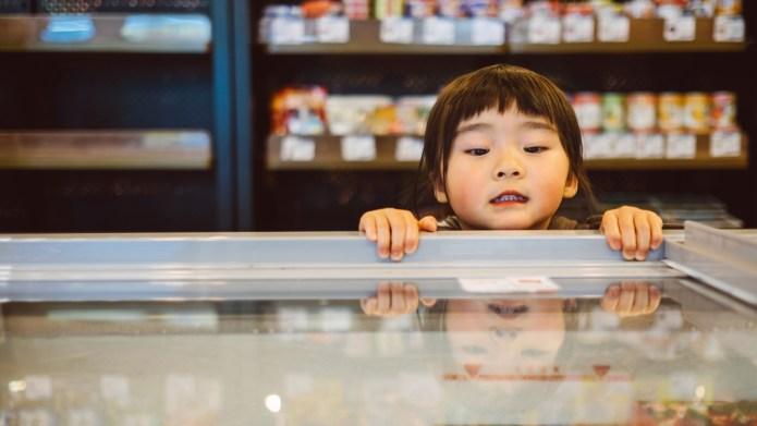 Little girl peeking into freezer in