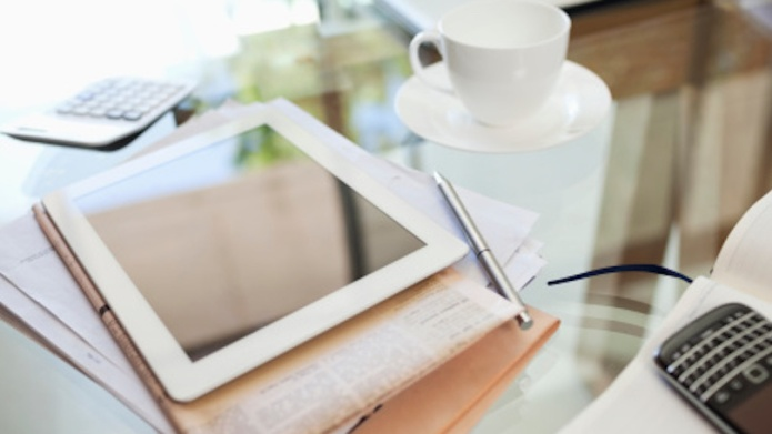 Tablet computer, newspaper, coffee cup and