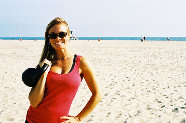 Woman on the beach with Kettle Bells