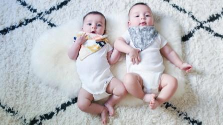 Boy/girl twins laying on blanket looking