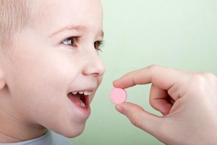 Kid taking a vitamin
