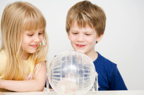 Kids playing with hamster in exercise ball