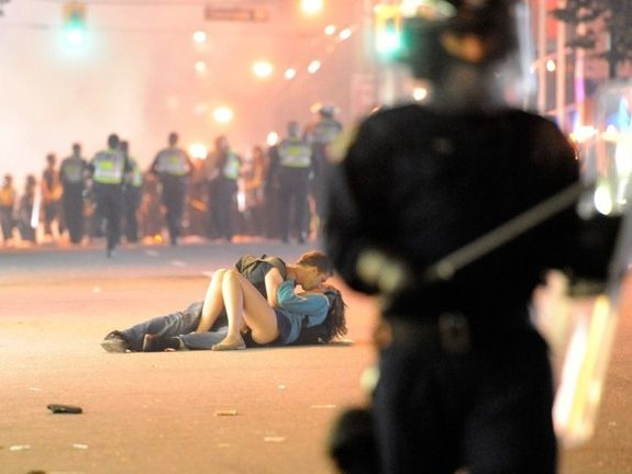 Couple kissing in middle of riot