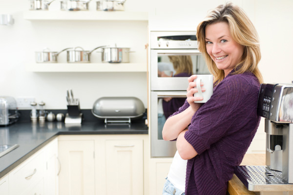Woman relaxing in organized kitchen