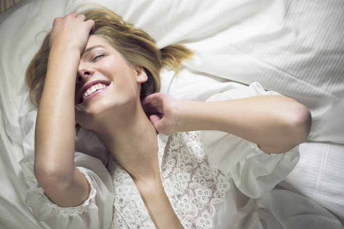 Young woman lying on bed with