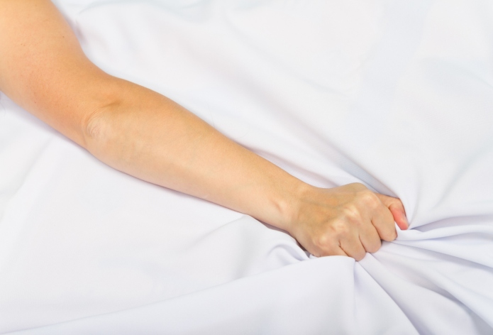 Female hand pulling white sheets in