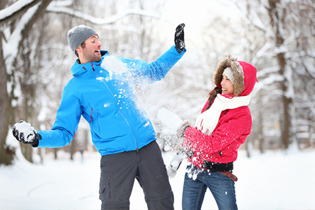 Laughing young couple snowball fight | Sheknows.ca