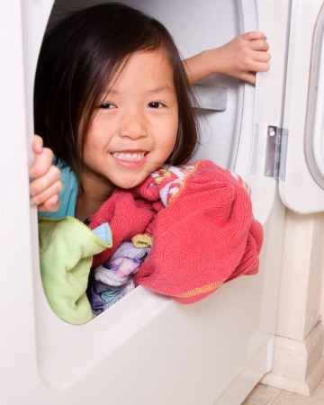 little girl playing in dryer