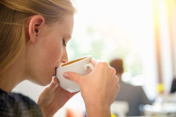 Young woman drinking coffee in cafe,