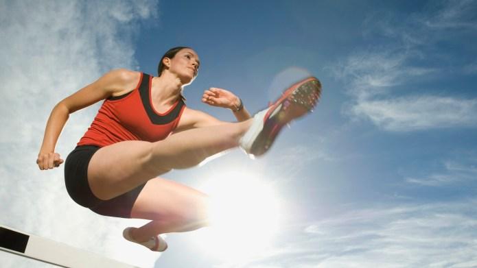 Female athlete jumping hurdle, Utah, United