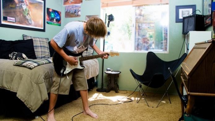 Teenage Boy Playing Guitar in Bedroom