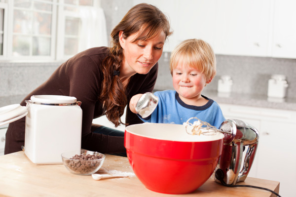 Little boy baking with mom