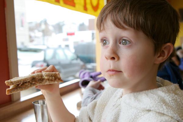 Little boy eating pbj